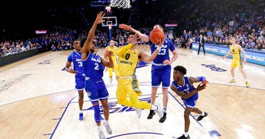 Marquette guard Markus Howard (0) goes up for a shot against Seton Hall players