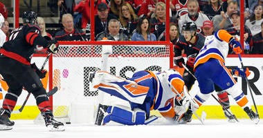 Carolina Hurricanes' Teuvo Teravainen, right, of Finland, scores against New York Islanders goalie Robin Lehner (40), of Sweden, while Islanders Anders Lee defends at right during the first period of Game 3 of an NHL hockey second-round playoff series in