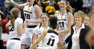 Iowa players including Megan Gustafson (10) and Hannah Stewart (21) celebrates in the closing seconds of the second half of a regional women's college basketball game against North Carolina State in the NCAA Tournament in Greensboro, N.C., Saturday, March