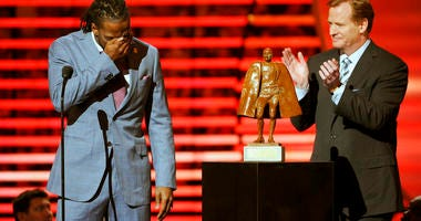 Charles Tillman of the Chicago Bears, left, accepts the award for Walter Payton NFL Man of the Year
