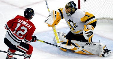 Chicago Blackhawks left wing Alex DeBrincat, left, scores against Pittsburgh Penguins goalie Casey DeSmith