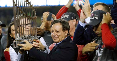 Boston Red Sox owner John Henry, partially hidden at left, and chairman Tom Werner holding the championship trophy beside manager Alex Cora