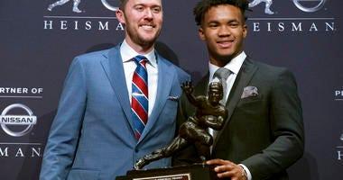 Oklahoma football coach Lincoln Riley, left, poses with Oklahoma quarterback Kyler Murray, winner of the Heisman Trophy