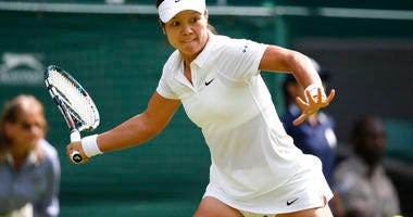 Li Na of China plays a return to Paula Kania of Poland during their first round match at the All England Lawn Tennis Championships in Wimbledon, London