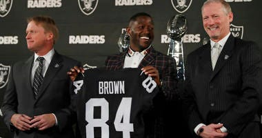 Oakland Raiders wide receiver Antonio Brown, center, holds his jersey beside coach Jon Gruden, left, and general manager Mike Mayock during an NFL football news conference Wednesday, March 13, 2019, in Alameda, Calif. (