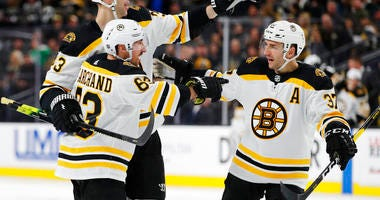 , Boston Bruins' Brad Marchand, front, celebrates with teammates Zdenoa Chara, back left, and Patrice Bergeron