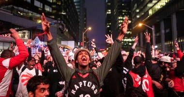 Toronto Raptors fans react as they watch Game 6 of the NBA basketball Eastern Conference finals between the Toronto Raptors and Milwaukee Bucks, on a screen outside Scotiabank Arena, in Toronto on Saturday, May 25, 2019.