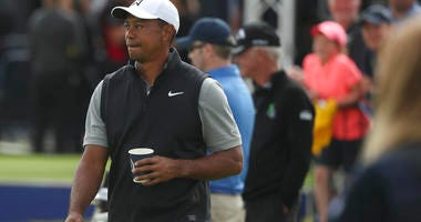 Tiger Woods of the United States holds a drink as he walks through the practice range ahead of the start of the British Open golf championships at Royal Portrush in Northern Ireland, Tuesday, July 16, 2019. The British Open starts Thursday.