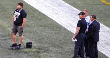 Officials assess the location where the CFL goal post holes were