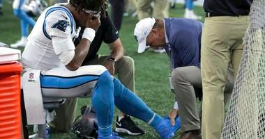 Carolina Panthers quarterback Cam Newton (1) receives attention on the sideline after an injury