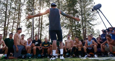 former Paradise High School football player Jeff Maehl, who played in the NFL, talks to the team after practice in Paradise, Calif.