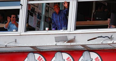 Cincinnati Reds announcer Marty Brennaman, center, waves to the crowd after the close of the fourth inning of a baseball game against the Milwaukee Brewers, Thursday, Sept. 26, 2019, in Cincinnati. (