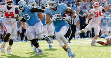 North Carolina's Beau Corrales (15) runs for a touchdown behind the block of Ed Montilus (63) while Clemson's Nyles Pinckney (44) looks on during the second quarter of an NCAA college football game in Chapel Hill, N.C., Saturday, Sept. 28, 2019.