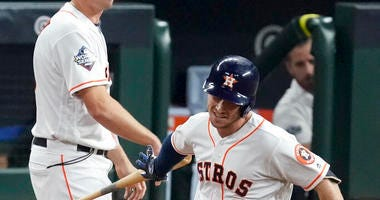 Houston Astros' Alex Bregman hand his bat to first base coach Don Kelly after a home run against the Washington Nationals during the first inning of Game 6 of the baseball World Series Tuesday, Oct. 29, 2019, in Houston.