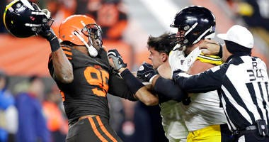 Cleveland Browns defensive end Myles Garrett, left, gets ready to hit Pittsburgh Steelers quarterback Mason Rudolph, second from left, with a helmet during the second half of an NFL football game, Thursday, Nov. 14, 2019, in Cleveland.