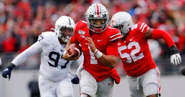 Ohio State quarterback Justin Fields, center, runs for a first down against Penn State during the first half of an NCAA college football game Saturday, Nov. 23, 2019, in Columbus, Ohio.