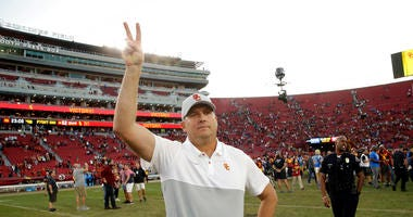 Southern California head coach Clay Helton signals to fans from midfield after a 52-35 win over UCLA in an NCAA college football game, Saturday, Nov. 23, 2019, in Los Angeles.