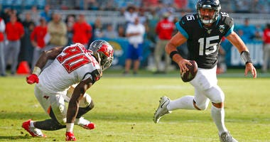 Jacksonville Jaguars quarterback Gardner Minshew (15) scrambles away from Tampa Bay Buccaneers linebacker Jason Pierre-Paul (90) during the second half of an NFL football game, Sunday Dec. 1, 2019, in Jacksonville, Fla.