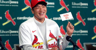 St. Louis Cardinals pitcher Kwang-Hyun Kim smiles as he holds up a sign during a news conference Tuesday, Dec. 17, 2019, in St. Louis. The Cardinals have signed the Korean left-hander to a two-year contract.