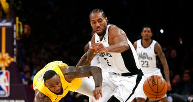 Los Angeles Lakers' LeBron James, left, and Los Angeles Clippers' Kawhi Leonard (2) chase the ball during the second half of an NBA basketball game Wednesday, Dec. 25, 2019, in Los Angeles. The Clippers won 111-106.
