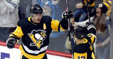 Pittsburgh Penguins' Evgeni Malkin (71) celebrates with Pittsburgh Penguins' Bryan Rust (17) after scoring against the Ottawa Senators during the first period of an NHL hockey game, Monday, Dec. 30, 2019, in Pittsburgh.