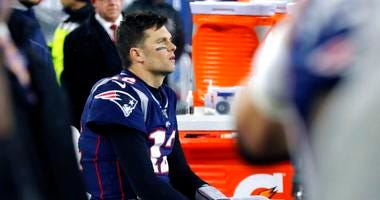 New England Patriots quarterback Tom Brady sits on the bench after throwing an interception that Tennessee Titans cornerback Logan Ryan returned for a touchdown late in the second half of an NFL wild-card playoff football game, Saturday, Jan. 4, 2020, in