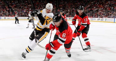 Andy Greene #6 of the New Jersey Devils takes the puck as Evgeni Malkin #71 of the Pittsburgh Penguins defends
