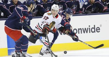 Columbus Blue Jackets defenseman Dean Kukan (46) and Jackets left wing Markus Hannikainen (37) defend Chicago Blackhawks left wing Graham Knott