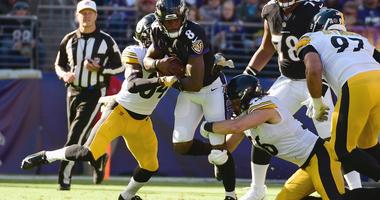 Baltimore Ravens quarterback Lamar Jackson (8) rushes as Pittsburgh Steelers strong safety Terrell Edmunds (34) and linebacker Anthony Chickillo (56) defends during the second quarter at M&T Bank Sta...