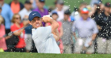 Rory McIlroy hits a golf shot out of a bunker.