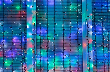 Outdoor Christmas lights decorate window in night