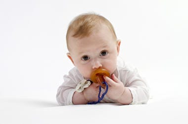 Cute baby boy lying on white studio background with dummy or pacifier in mouth.