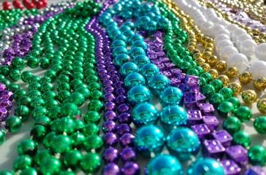 Purple green blue gold and white beads from New Orleans Mardi Gras celebration. View is level with the objects and perspective is moving away from camera. These are long strands of round beads.
