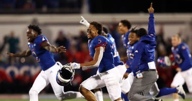 Wide receiver Stephon Robinson Jr. #5 and the Kansas Jayhawks storm the field and celebrate as they defeat the Texas Tech Red Raiders 37-34 to win the game at Memorial Stadium on October 26, 2019 in Lawrence, Kansas.