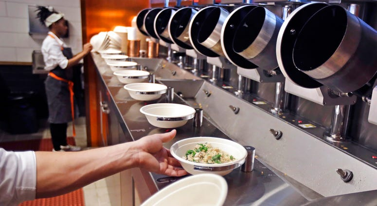 A worker lifts a lunch bowl off the production line at Spyce, a restaurant which uses a robotic cooking process, in Boston, Thursday, May 3, 2018.