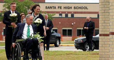 Gov. Greg Abbott, his wife, Cecilia, Lt. Gov. Dan Patrick, along with Sen. Larry Taylor and Rep. Greg Bonnen prepare to place flowers Sunday, May 20, 2018, at Santa Fe High School.