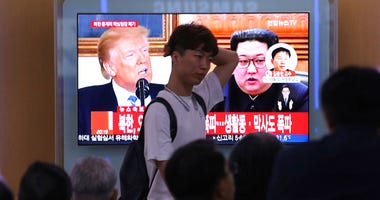 People watch a TV screen showing file footage of U.S. President Donald Trump, left, and North Korean leader Kim Jong Un.