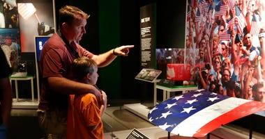"Visitors to the National September 11 Memorial & Museum view the ""Comeback Season: Sports After 9/11"" exhibit."