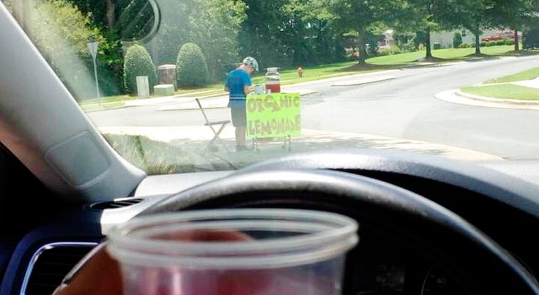 This Saturday, Aug. 4 2018, photo provided by James Castellano, of Monroe, N.C., shows a drink he bought from a boy, background, in Monroe