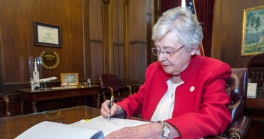 Alabama Gov. Kay Ivey signing a bill that virtually outlaws abortion in the state, in Montgomery, Ala.