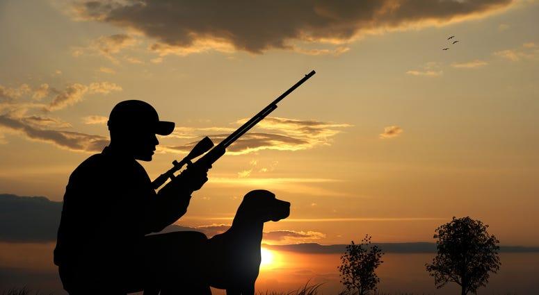 hunter with rifle and dog
