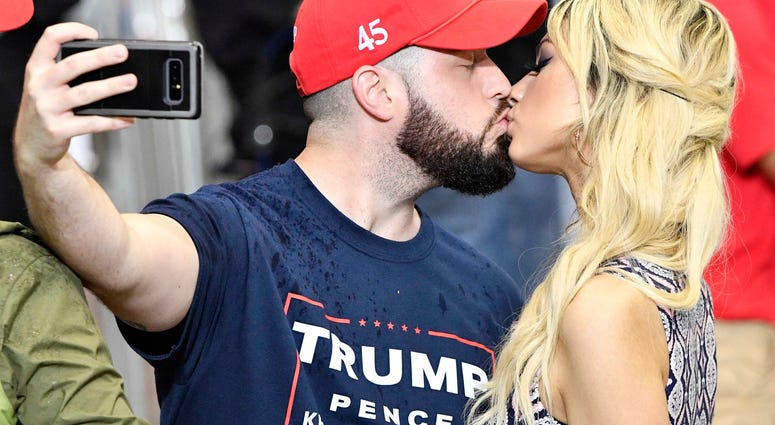 A couple kisses in line and takes a selfie before the rally by President Donald Trump at Municipal Auditorium.