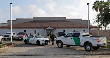U.S. Border Patrol Agent walks between vehicles outside the Central Processing Center in McAllen, Texas