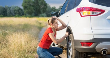 Woman struggling to change flat car tire on countryside road
