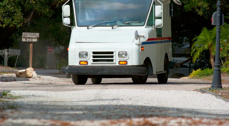 Mail delivery truck on a residential road on a sunny day