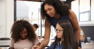 Teacher helping high school students with technology