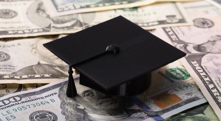 graduation cap atop dollar bills