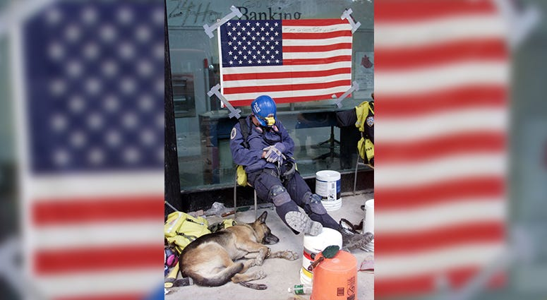 A canine officer and his dog rest September 18, 2001 after search duty at the site of last week's New York World Trade Center terrorist attack.