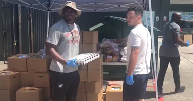 Washington running back Adrian Peterson and Astros infielder Alex Bregman help provide fresh food to Spring Branch students.
