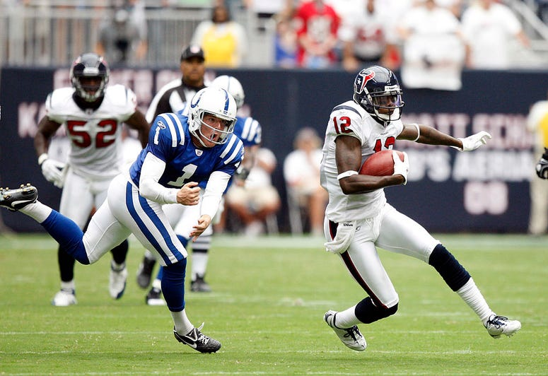 Jacoby Jones #12 of the Houston Texans avoids kicker Pat McAfee #1 of the Indianapolis Colts on the opening kick return during the NFL season opener at Reliant Stadium on September 12, 2010 in Houston, Texas.